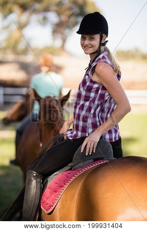 Portrait of woman horseback riding with friend sitting on horse in background during sunny day