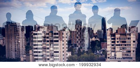 Colleagues standing over white background against trees amidst buildings in city