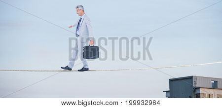 Side view of businessman walking with briefcase over white background against cropped image of building against sky