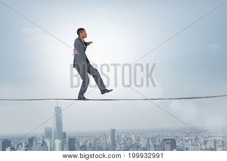 Businessman performing a balancing act against balcony overlooking city