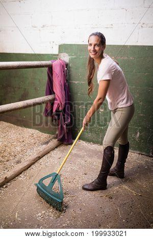 Full length portrait of female jockey cleaning stable