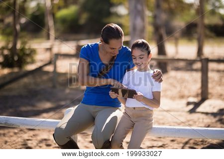 Smiling sisters using tablet computer while sitting on railing at paddock