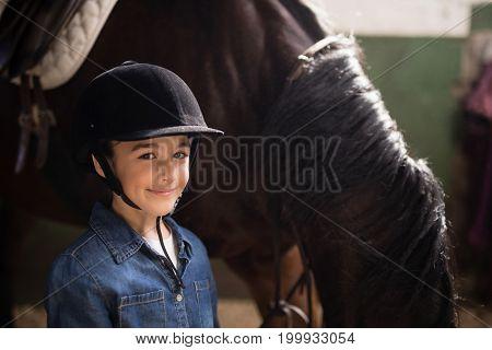 Portrait of girl wearing helmet standing by horse instable
