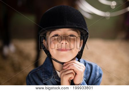 Portrait of smiling girl fastening helmet while standing in stable