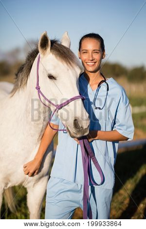 Portrait smiling female vet by horse standing on field