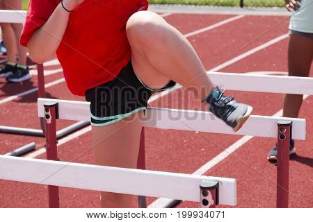 A high school track and field athlete at practice going over hurdles on a red track over the summer.