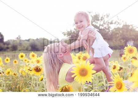 Family Is Walking Along The Summer Flowering Field. Happy Mother And Daughter In The Sun. Summer. Su