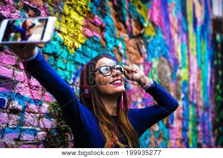 Fashion pretty carefree woman listening music in headphones in colorful abstract background
