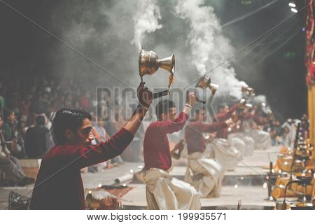 Varanasi, India - January 25, 2017: Waving Kapoor Lamps. Crowds Watch As Priests Perform The Ganga A