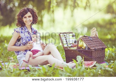 Young Beautiful Mother Sits With Her Daughter On Blanket In Park.