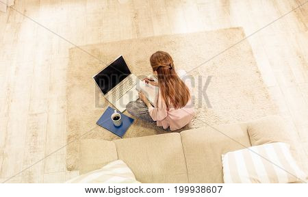 Young woman studying sitting on carpet with her back to camera. Learning at home, girl drinking coffee, making notes and working with laptop.