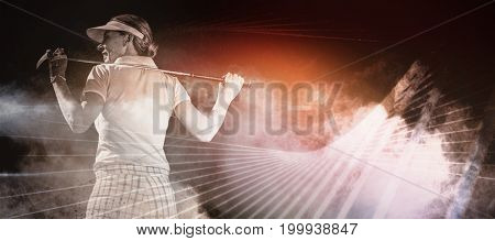 Woman playing golf against digitally generated image of color powder