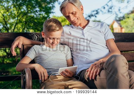 smiling preteen boy using smartphone with grandfather near by while resting in park