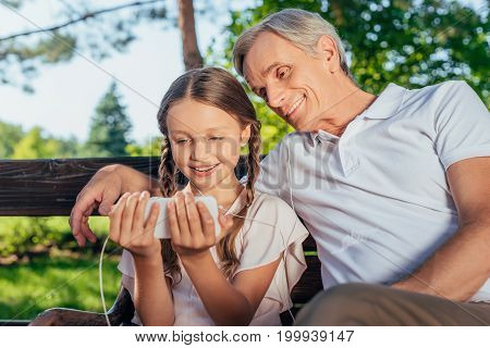 smiling grandfather and little girl using smartphone together in park