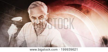 Man holding a golf club against splashing of blue color powder
