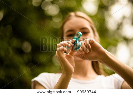 Close up view of fidget spinner in hands of young girl. Female outdoors playing with modern spinner.