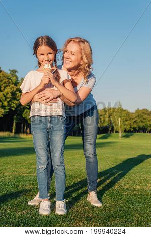 smiling grandmother hugging preteen girl with ice cream on meadow