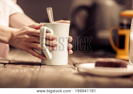 Female hands holding a white cup of tea standing close to wooden desk. Close up view of mug with teaspoon inside.