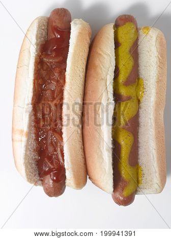 Two Hot Dogs on a White Background with Mustard and Red Onions