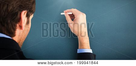 Businessman writing with a white chalk against blue