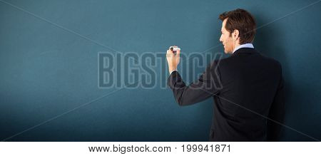 Businessman standing back to camera writing with marker against blue