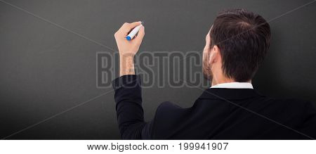 Rear view of businessman writing with marker against grey