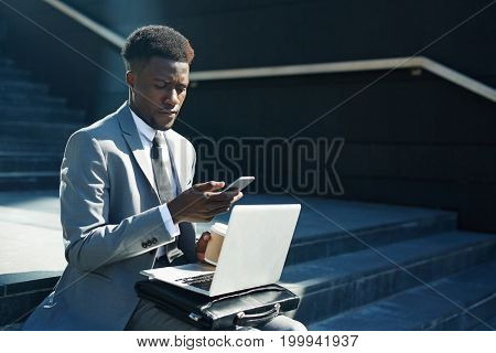 Businessman with laptop and smartphone sitting on stairs in the street