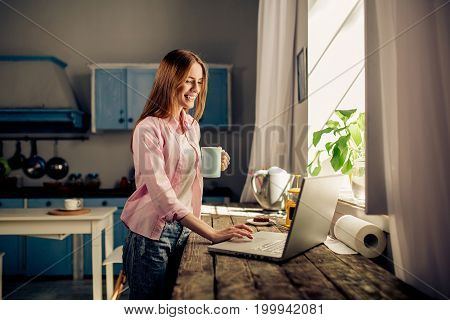 Home interior, female staying at home in the morning. Portrait of pretty girl standing in the kitchen keyboarding on laptop, holding cup.
