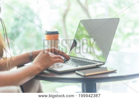 Side view of female hands using laptop with coffee and smartphone beside