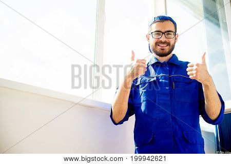 Construction worker installing window and showing thumbs up