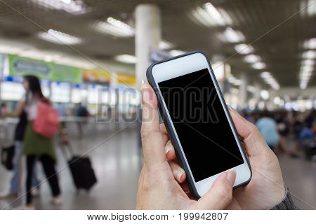 Woman hand holding and using mobilecell phonesmart phone with isolated screen with blur image of people for background.