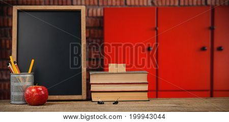 Books by slate with desk organizer and apple on wooden table against closed orange lockers against brick wall