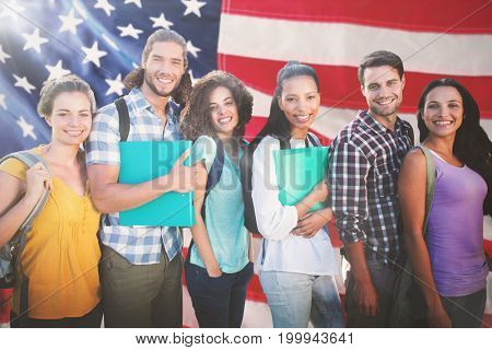 Smiling group of students standing in a row against close-up of an flag