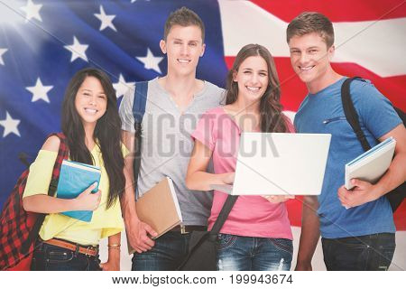 A smiling group of students holding a laptop while looking at the camera against close-up of us flag