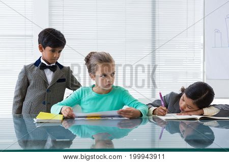 Businessman looking at businesswomen working at table in boardroom