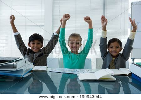 Portrait of cheerful business people with arms raised sitting in boardroom