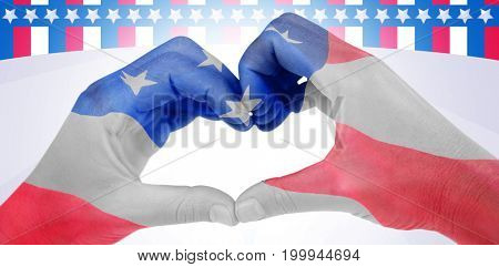 Woman making heart shape with hands against american flag with stars and stripes