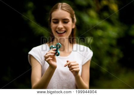 Girl playing with fidget spinner smiling. Modern gadget for relaxation, happy woman enjoying spinner game, camera focused on hand holding toy.
