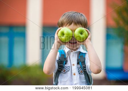 Child With Book And Green Apple Outdoors