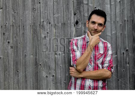 Portrait of thoughtful young man in shirt smiling while standing against wooden background.