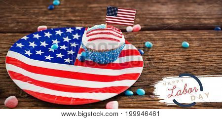 Digital composite image of happy labor day text with blue outline against cupcake with american flag in plate
