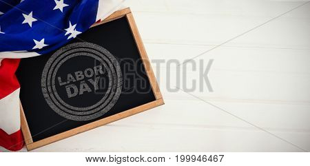 Labor day text in circles against american flag and slate on table
