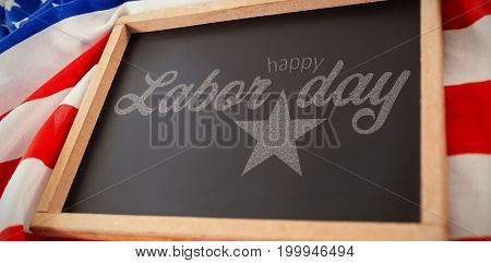 Digital composite image of happy labor day text with star shape against empty slate over american flag  on table