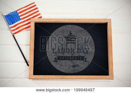 Digital composite image of celebrate labor day text with American flag on blue poster against blank chalkboard by american flag