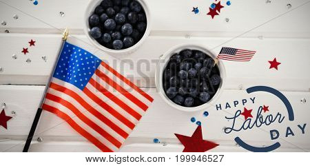 Digital composite image of happy labor day text with blue outline against overhead view of blueberries in bowls with american flag