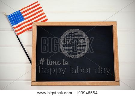 Digital composite image of time to happy labor day text against chalkboard and american flag on table
