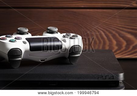 Sankt-Petersburg, Russia - 14 August, 2017: Sony PlayStation 4 Slim 1Tb revision and game controller on the wood surface.