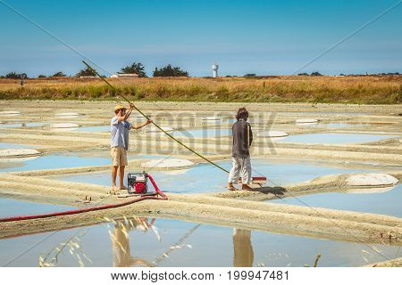 Two Men Harvest Salt In The Traditional Way In The Salt Marshes