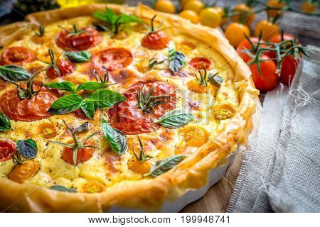 Tomato pie on rustic wooden background .
