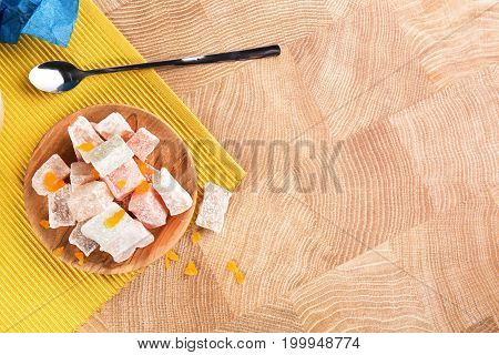 View from above of a plate full of many fruit turkish delight on a yellow fabric on a wooden table background. Ingredients for sweet, organic, nutritious desserts. Copy space.